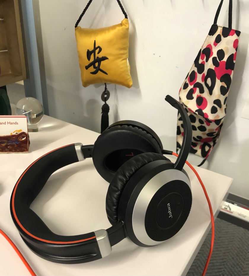 headphones on a desk, with a mask and a peace pillow in Japanese.